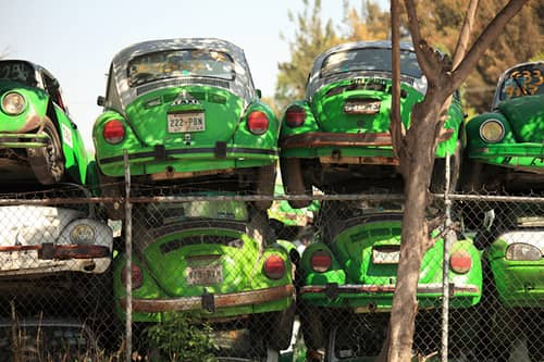 green volkswagen beatle cars in junkyard