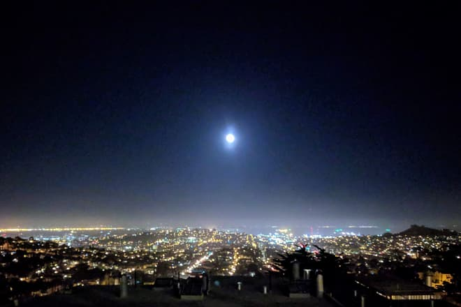 Looking east across San Francisco at night. The Moon is high in the sky, and the other side of San Francisco Bay can just be seen on the horizon.