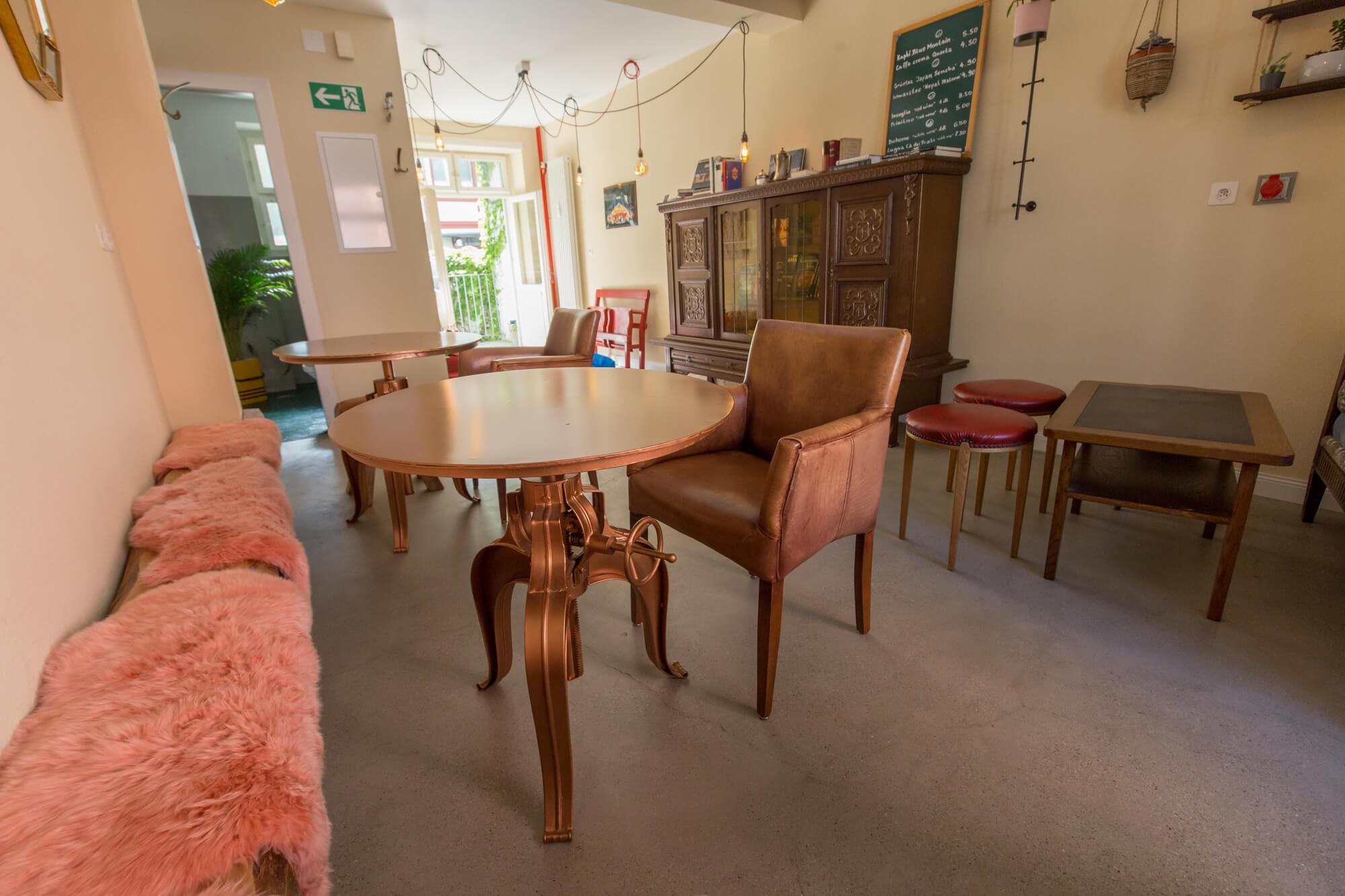 Kaffeebar mit antiken Leder-Stühlen und metallenen Tischen