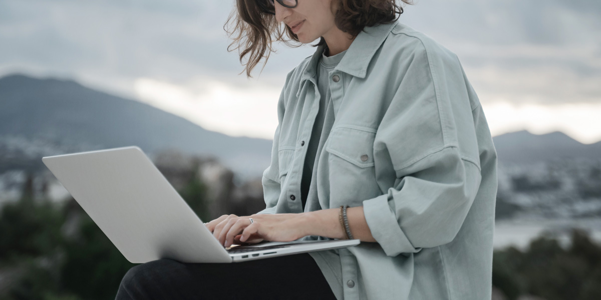 A user interface designer sitting against a mountainous background, typing on a laptop