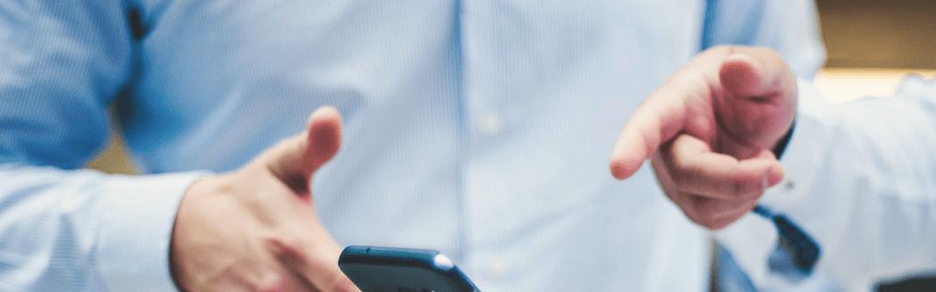 Zwei Männer zeigen auf Smartphone