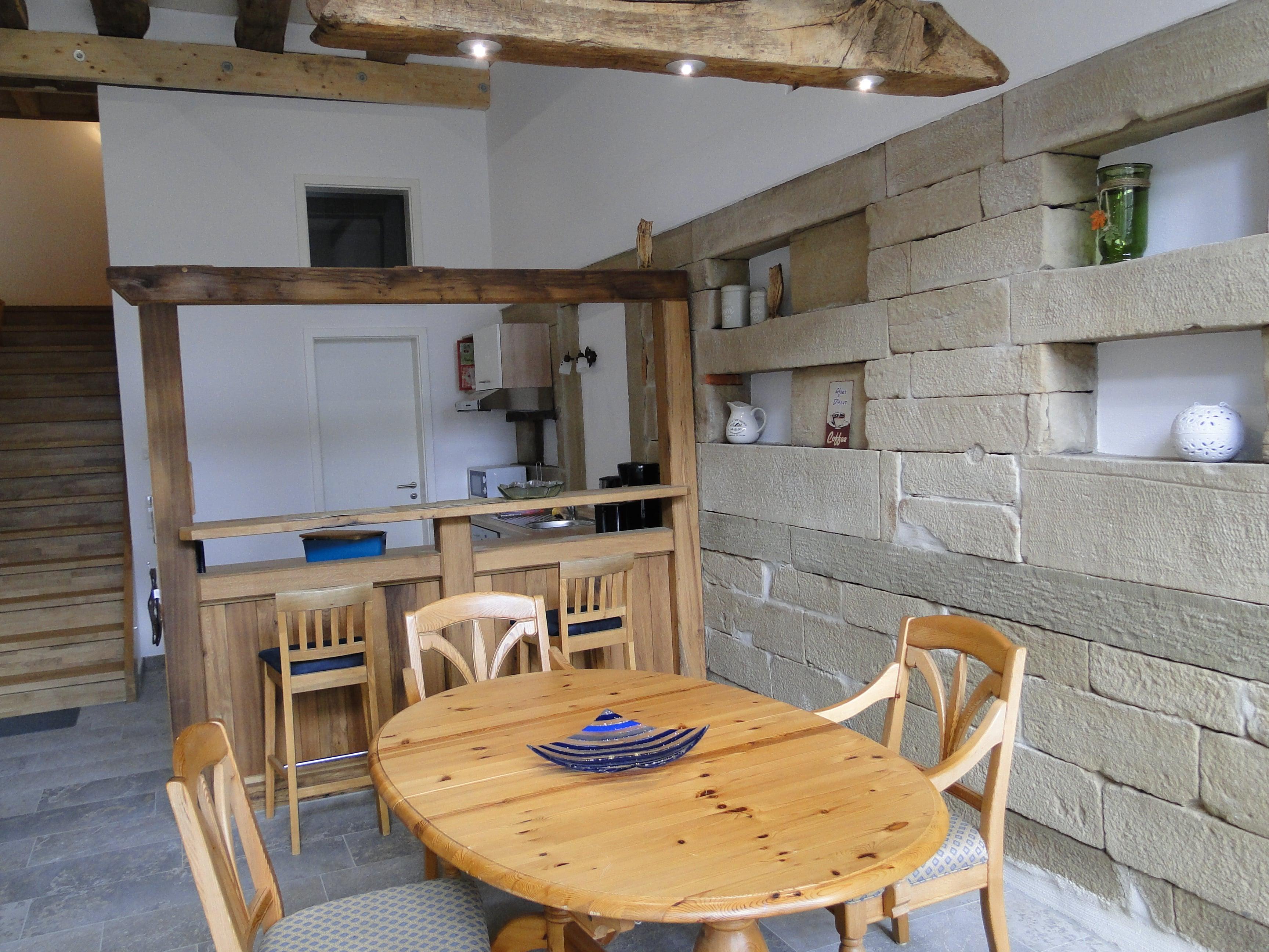 Lichtdurchflutetes Esszimmer mit Tisch und Küchenbar im Hintergrund