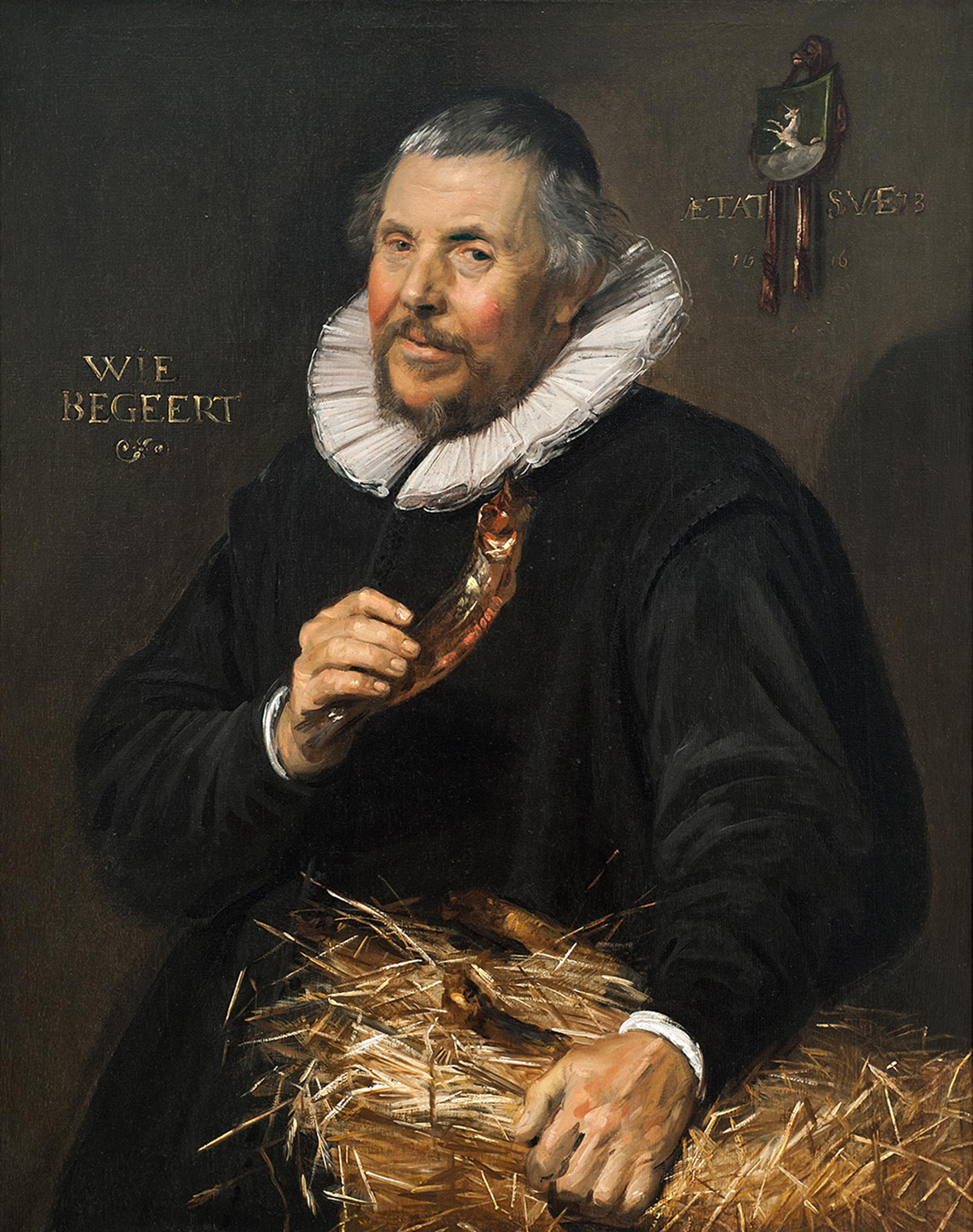Portrait of older man holding a dried herring. His other hand rests on a bale of hay.