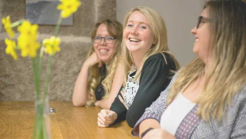 Three women happy sitting at wooden table with yellow flowers to celebrate UK advisory firm The Peloton gain 60% referral rate with Futrli as advisors and accountants with clients #referral