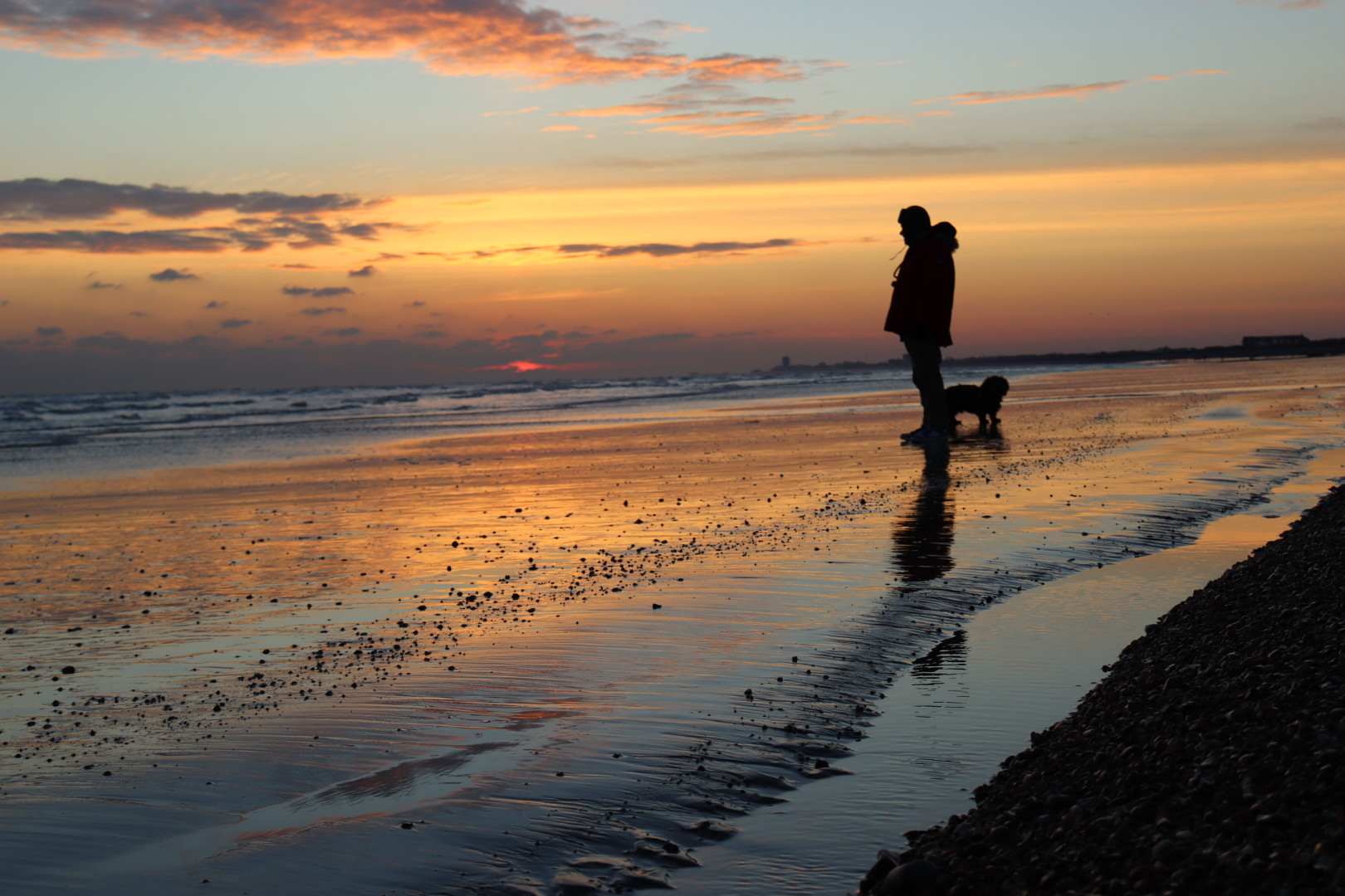 Silhouette of a man and dog. Stood on sand as the tide rolls out into the horizon. Sunset behind them obsucred by clouds.