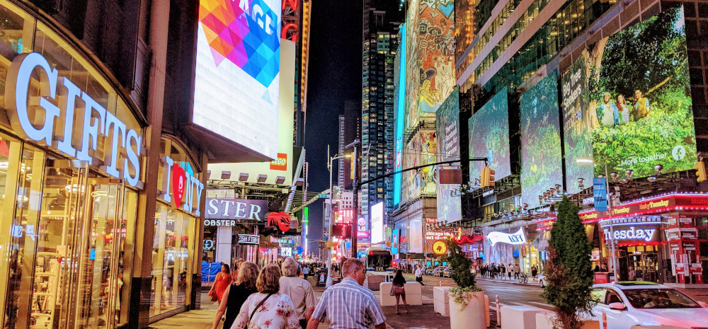 An image of Times Square in New York City at night. It is very chaotic