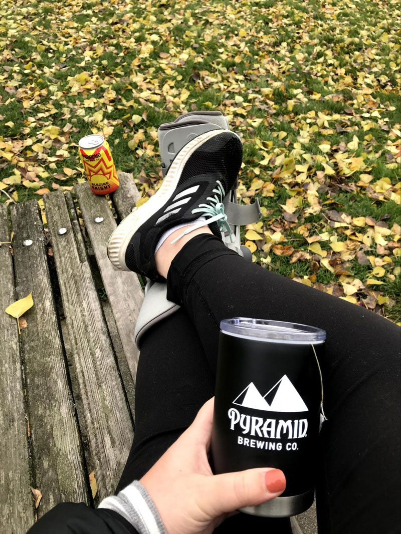 Legs and hands of a woman sitting casually on a wooden bench with yellow fall leaves in the background. The hand is holding a can of Pyramid Beer.