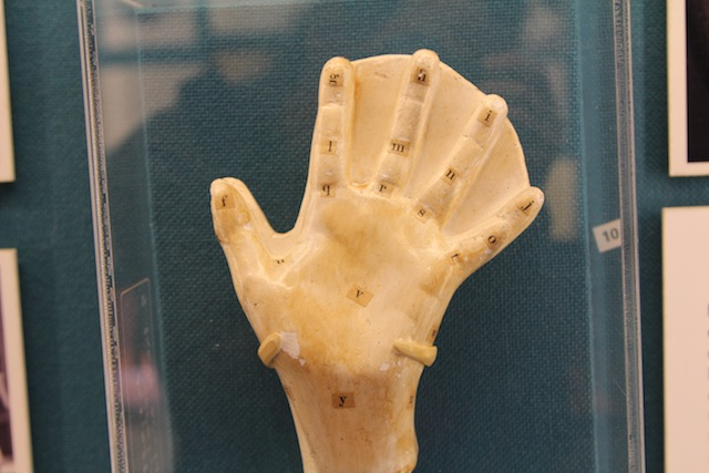 A ceramic adult-sized sculpture of a hand, with letters at each knuckle joint and finger tip.