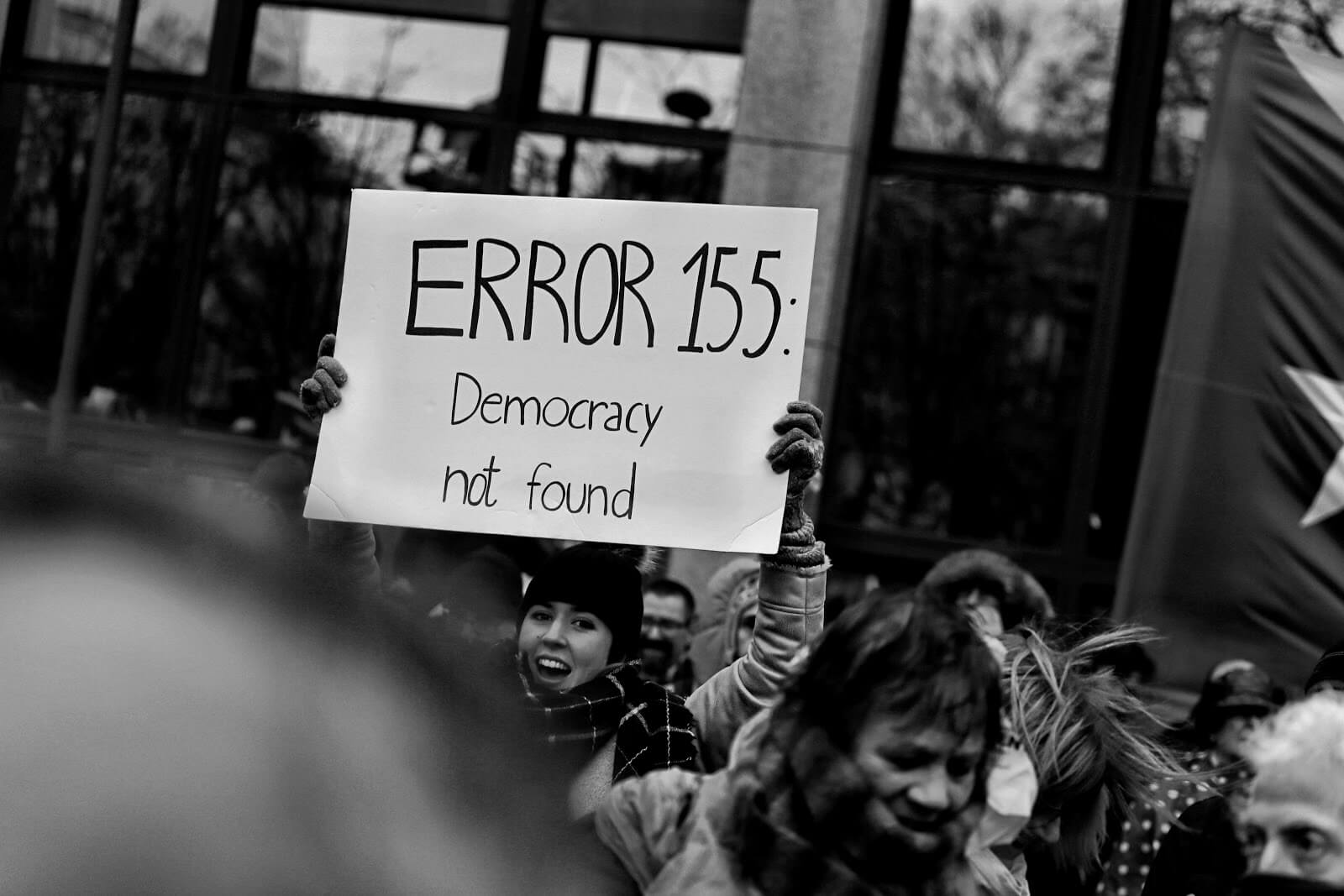 A woman in a crowd holding a sign that says ERROR 155: Democracy not found.