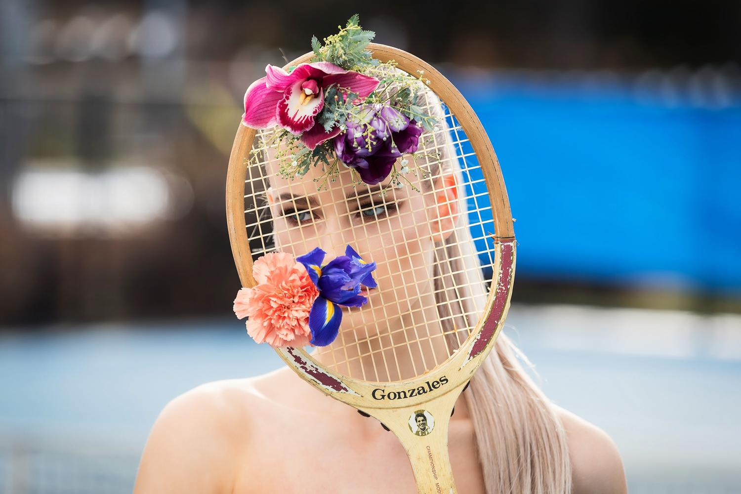 Women holding a tennis racquet with flowers