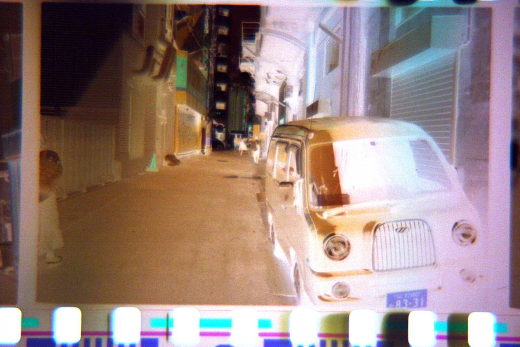 Photographic Negative of a car in an alleyway, now with less brown because the colour has been corrected