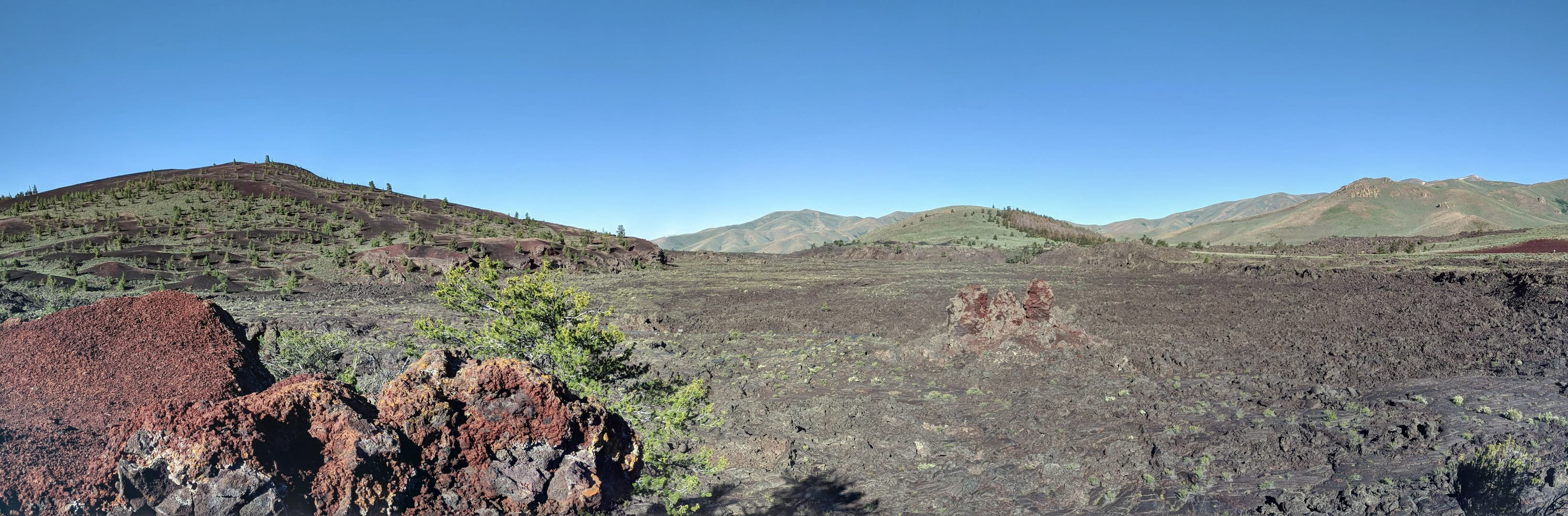 A black, jagged lava field, barely colonized by desert scrub. Three large, red rock pillars rise from it. In the distance are a set of low, scrub- and pine-covered rises of obvious volcanic origin.