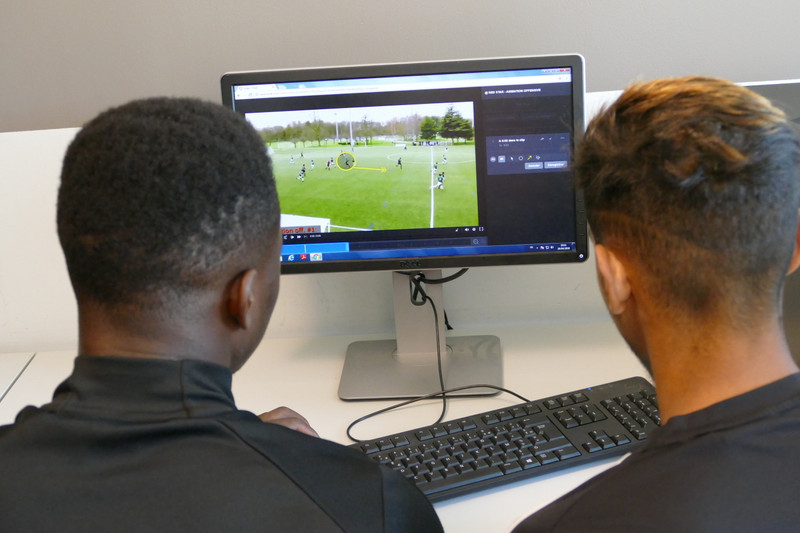 Two players analyse soccer video gameplay at monitor