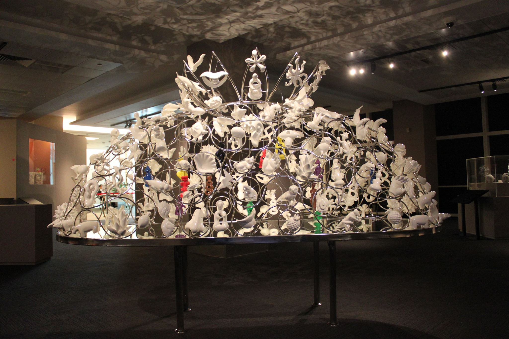 A large work sits on a metal table. It is a dome made up of smaller pieces of sculptures, strung together with wire.