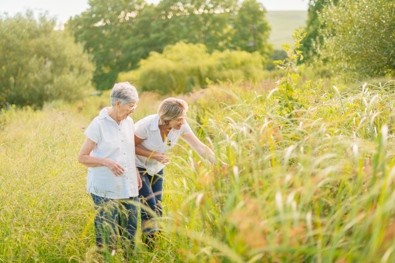 Two women walking in a beautiful field.