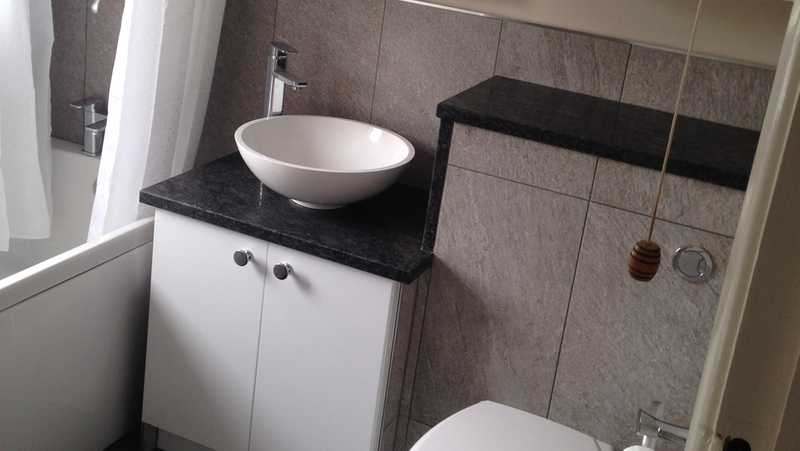 A newly fitting bathroom suite, with tiled boxing around a vanity unit