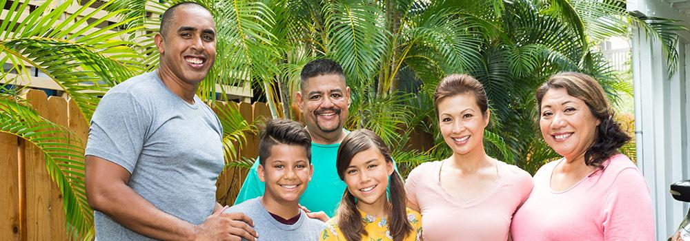 A family with healthy teeth is smiling for a group photo.