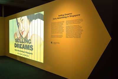 The exhibition introduction wall. A trivision-style video is projected onto the wall, next to the introduction text.