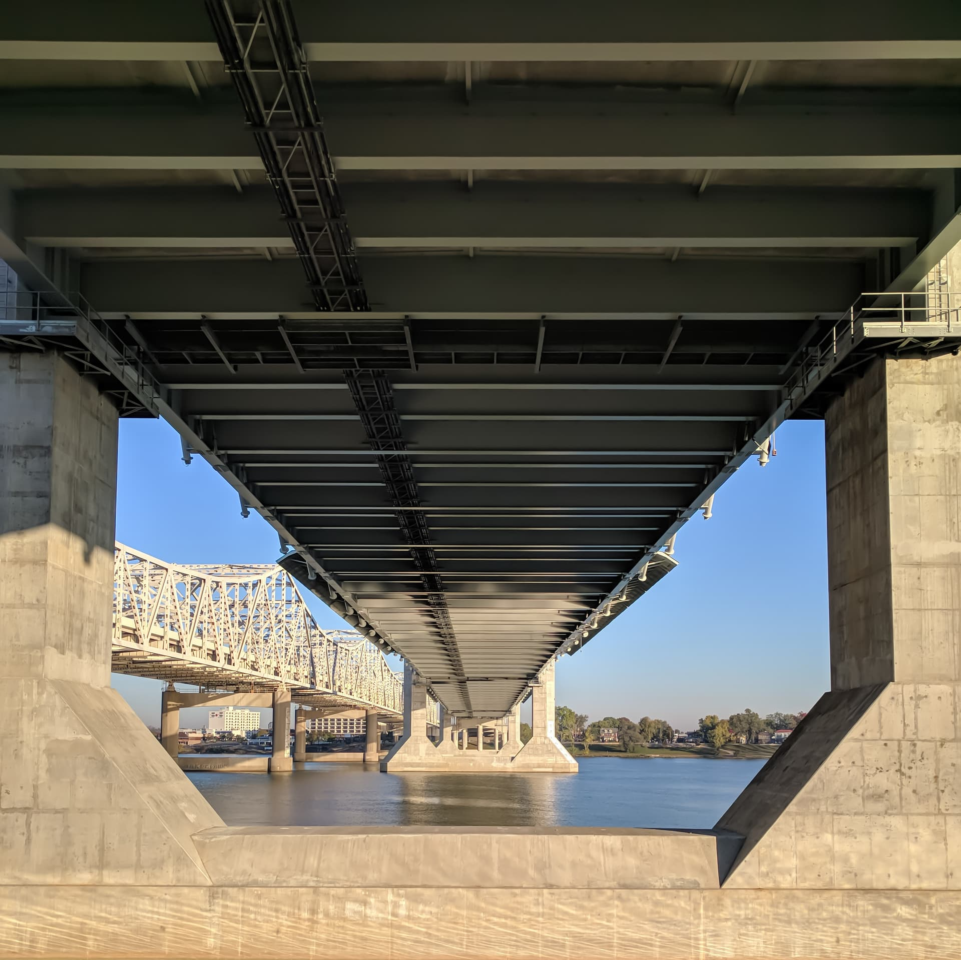 Looking towards Indiana across the Ohio River from underneath a bridge. The shot is framed by the bridge's concrete pylons, which regularly recede into the distance.