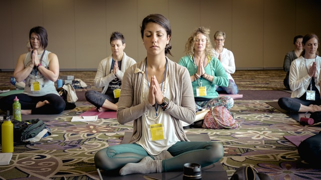 Women in a conference room meditating