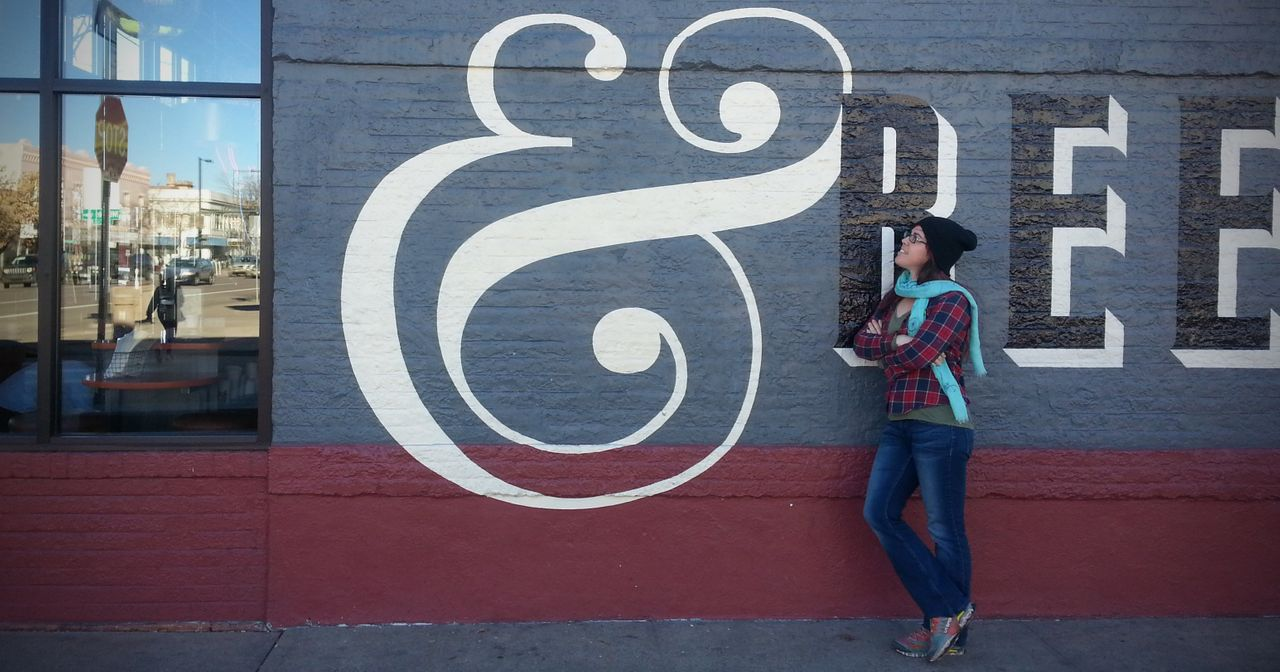 Sondra looks at large ampersand symbol painted on building exterior