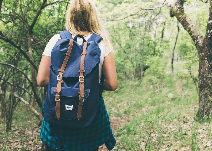 Lady with backpack walking through woods