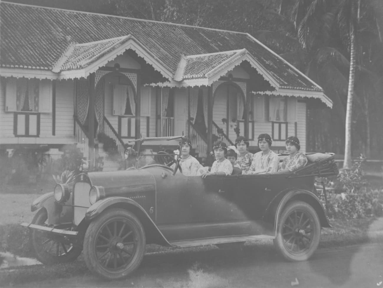 Motor car with female driver and passengers, 1920s