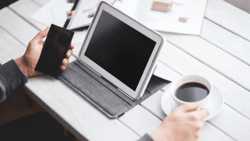 An accountant/business owner uses tablet and phone with coffee cup on desk with documents to use 7 best quickbook apps for businesses #productivity