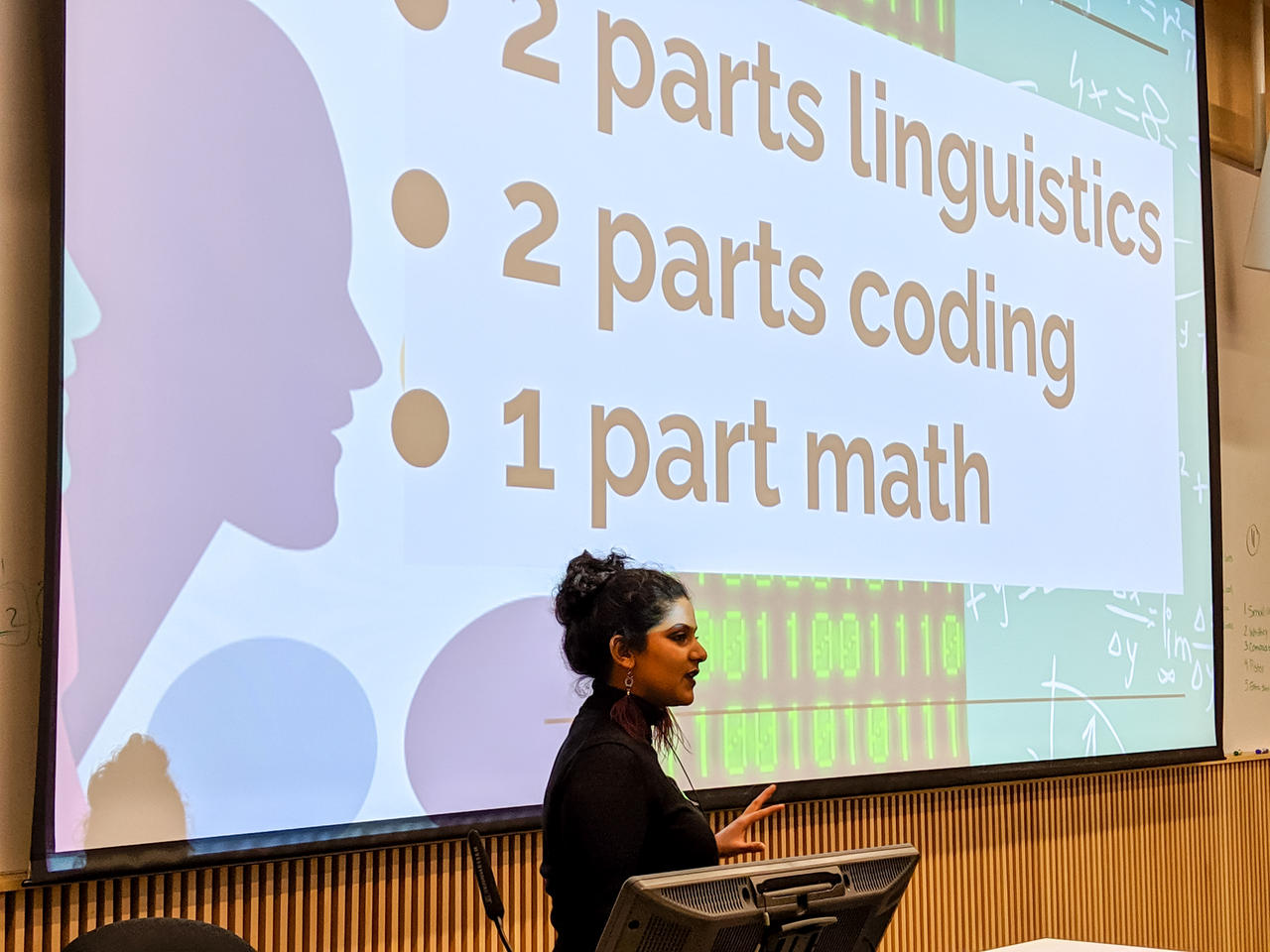 Vasundhara is standing and presenting in front of a screen where one of xyr slides is projected. The slide has three bullet points that say: 2 parts linguistics, 2 parts coding and 1 part math, which is xyr formula for xyr personal sweet spot with computational linguistics.