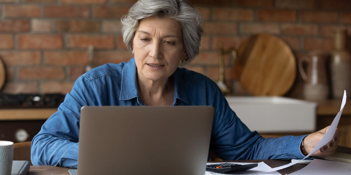 A data analyst sitting at a desk with a brick wall behind them, looking at a laptop screen, holding a piece of paper in their hand