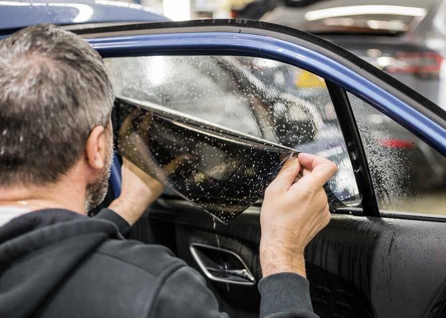 Car rear window being tinted using dark UV protection film