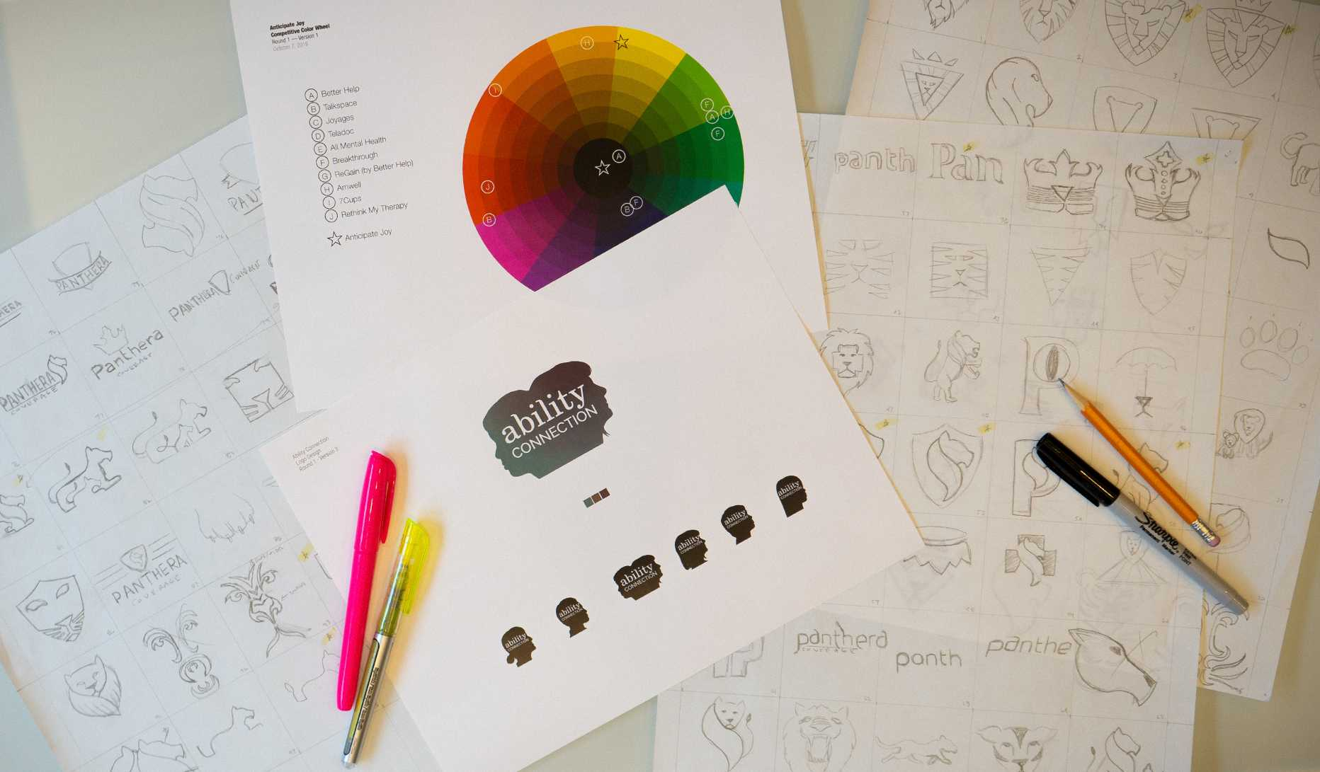 Table with logo sketches, color wheel and logo printout