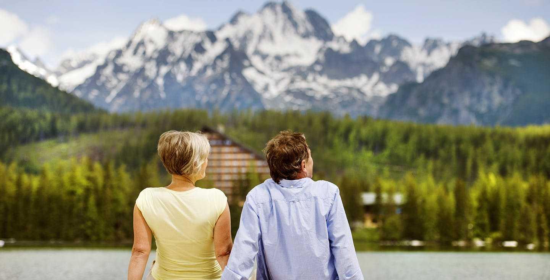 Älteres Paar sitzt auf einem Steg mit Blick in die Berge - Rentenpunkte - was ist das eigentlich und was bringen sie mir