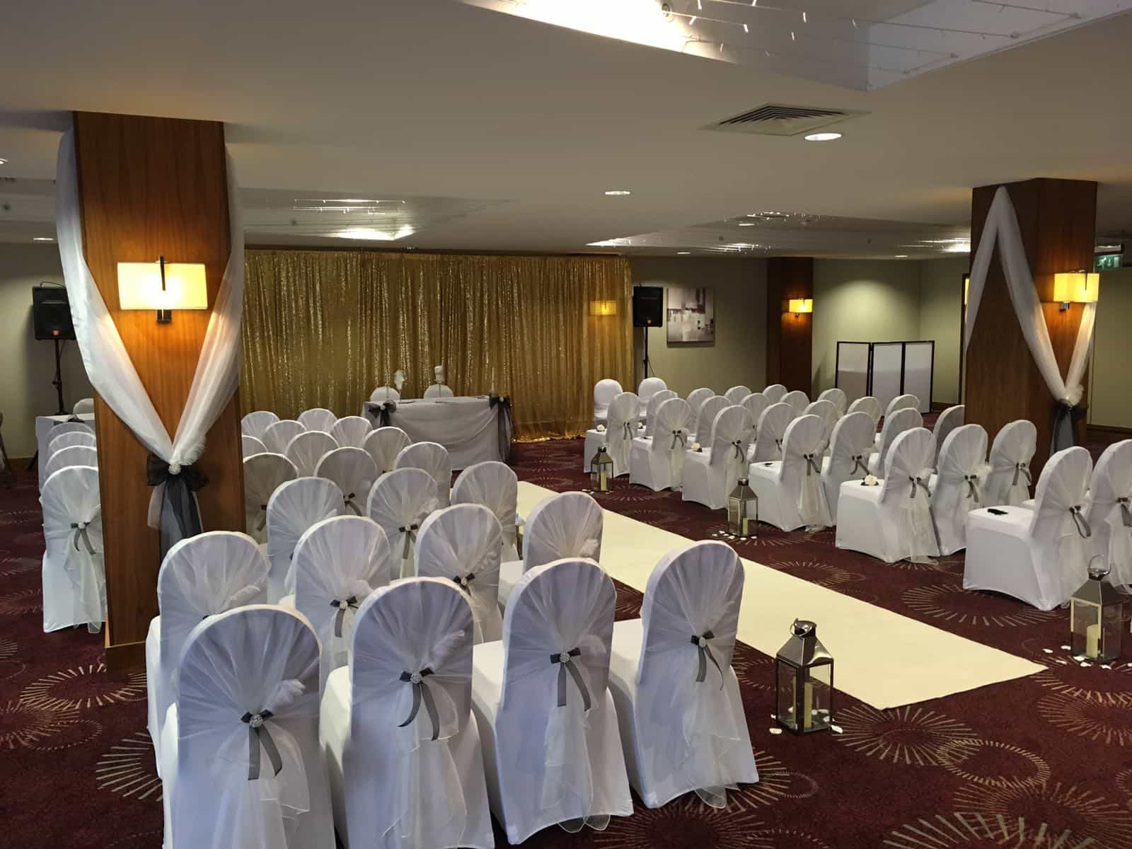 Wedding ceremony with white aisle runner surrounded by pretty white chairs