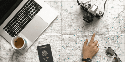 Business person, entrepreneur points at map atlas with camera, laptop, passport, coffee and sunglasses on to plan travel hacks through getting their cashflow right #entrepreneur