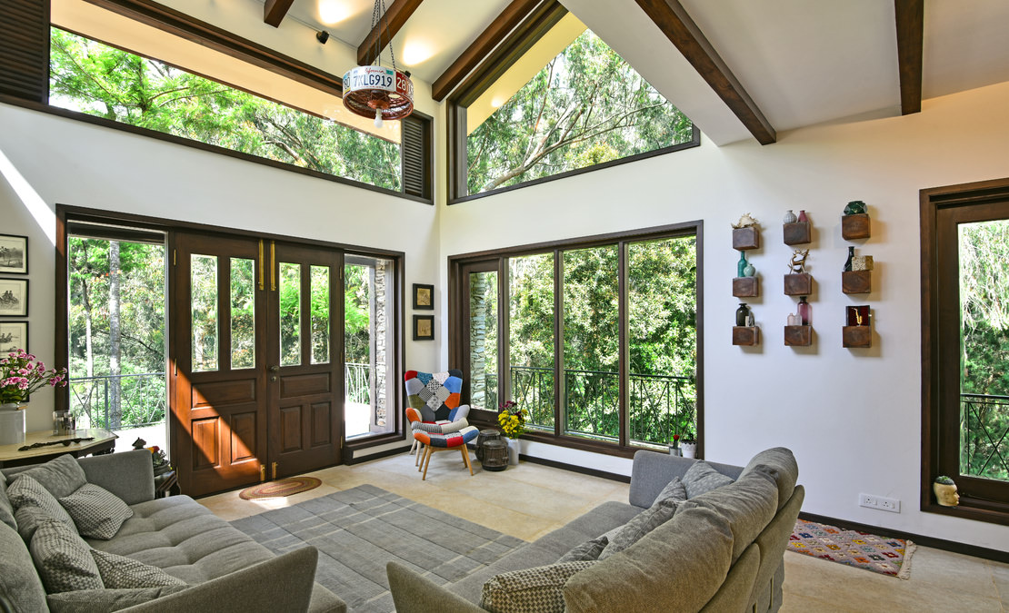 High ceiling and tall glass panes, looking into the forest, gives you the perfect feel of holidaying in the Nilgiris