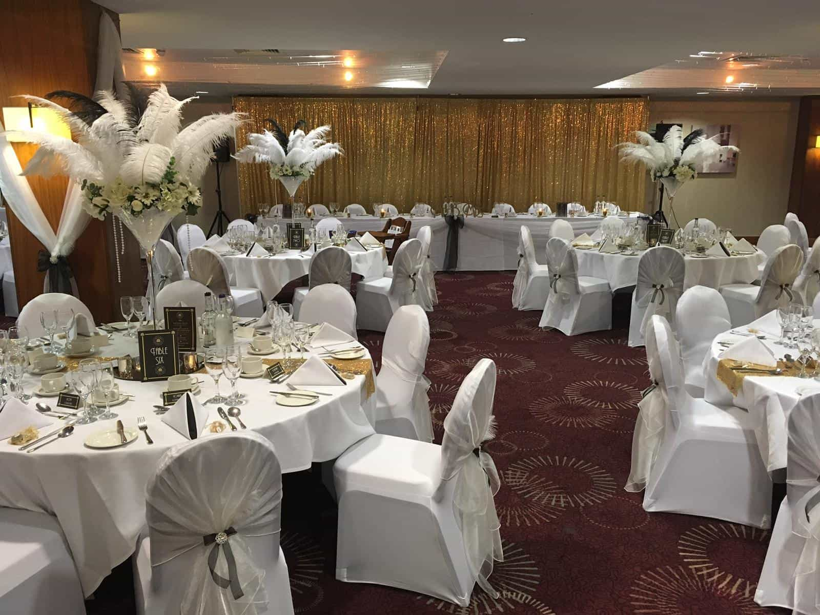 beautiful wedding venue dressing with white plumes as table centrepieces and white table and chair linen