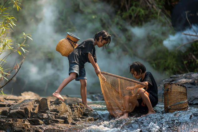 Children fishing with baskets in a river