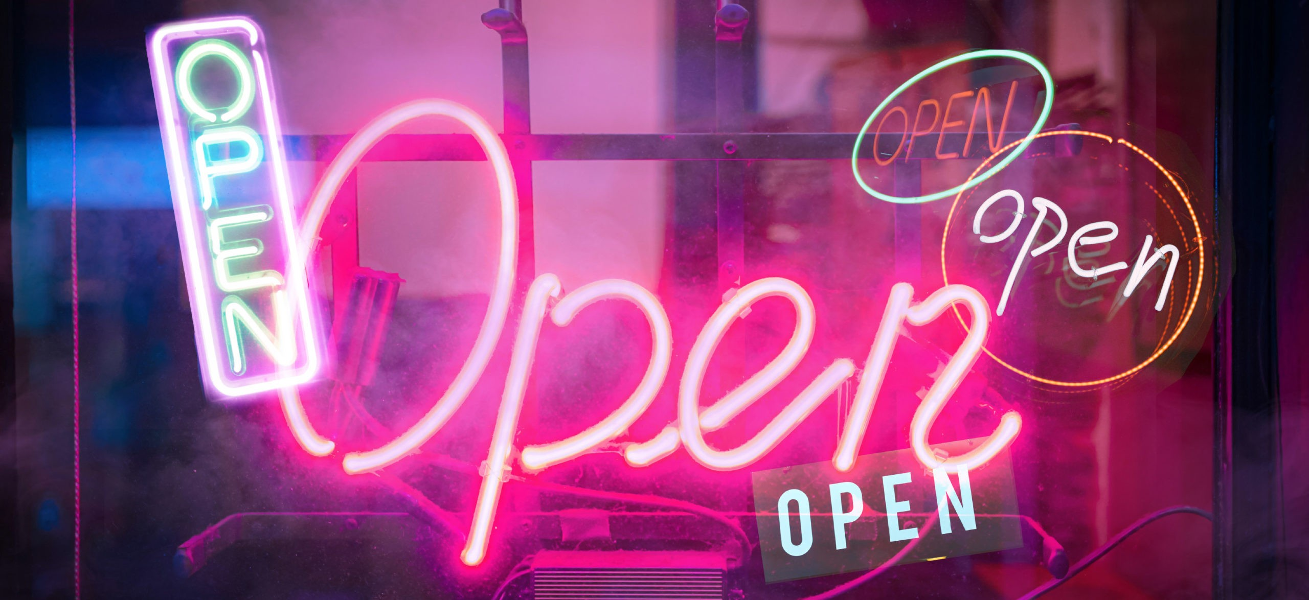 """A photo illustration of several neon """"Open"""" signs alight in the dark to signify re-opening of society after COVID-19"""