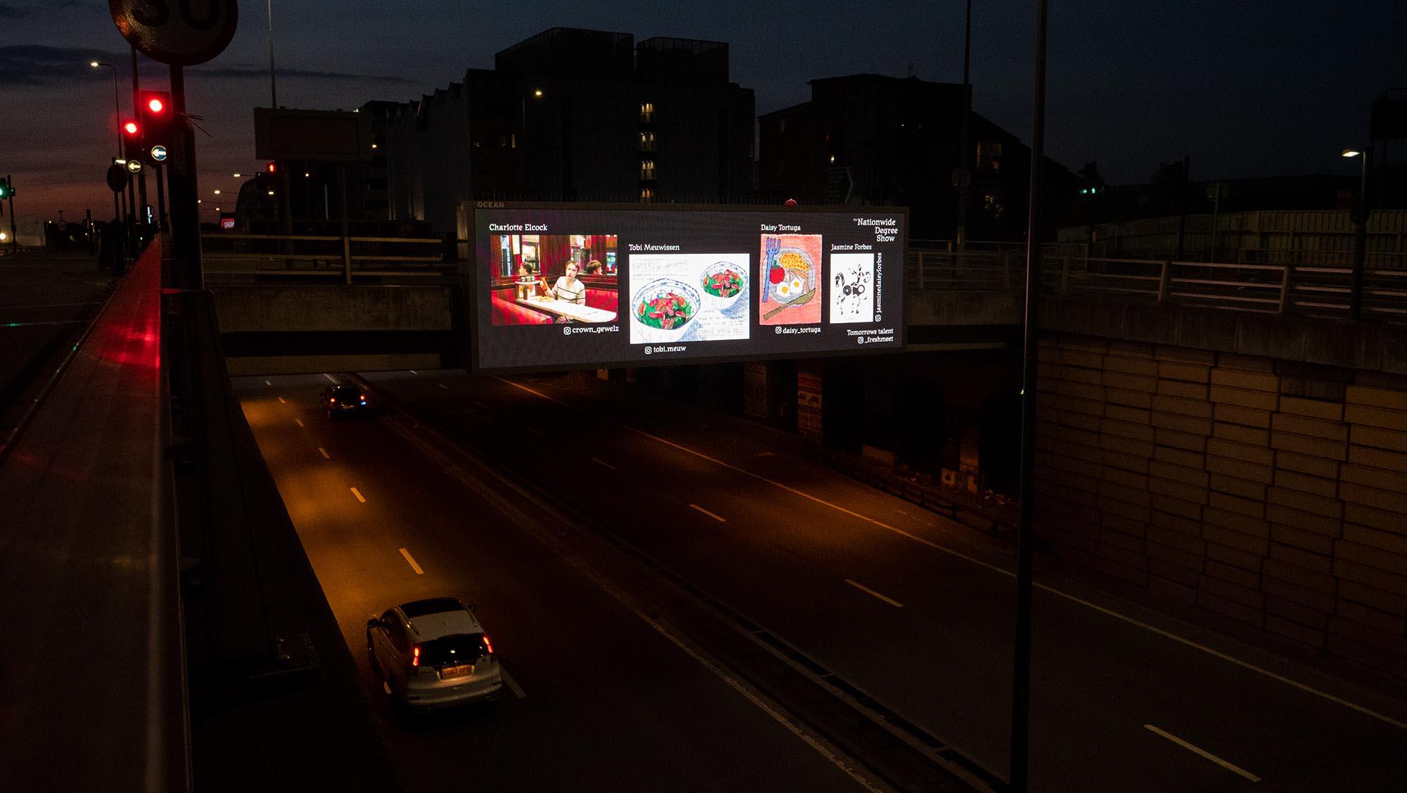 Billboard showing graduate work at night