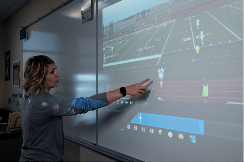 Woman pointing to video projection of soccer match on whiteboard