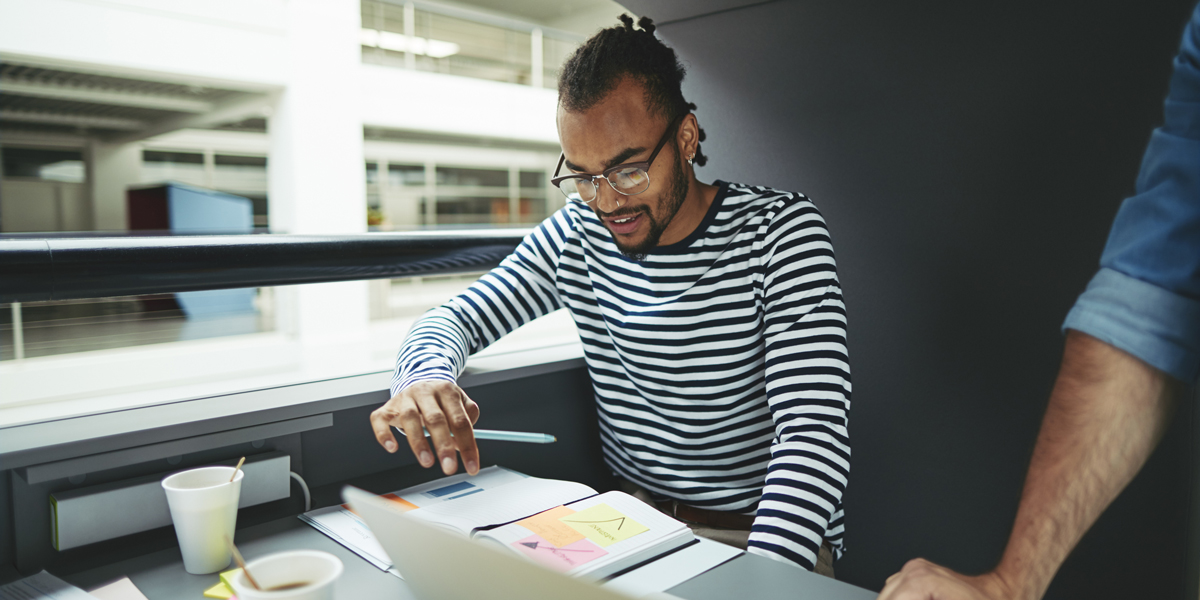 UI designer sitting down and choosing a font with his laptop and some notes