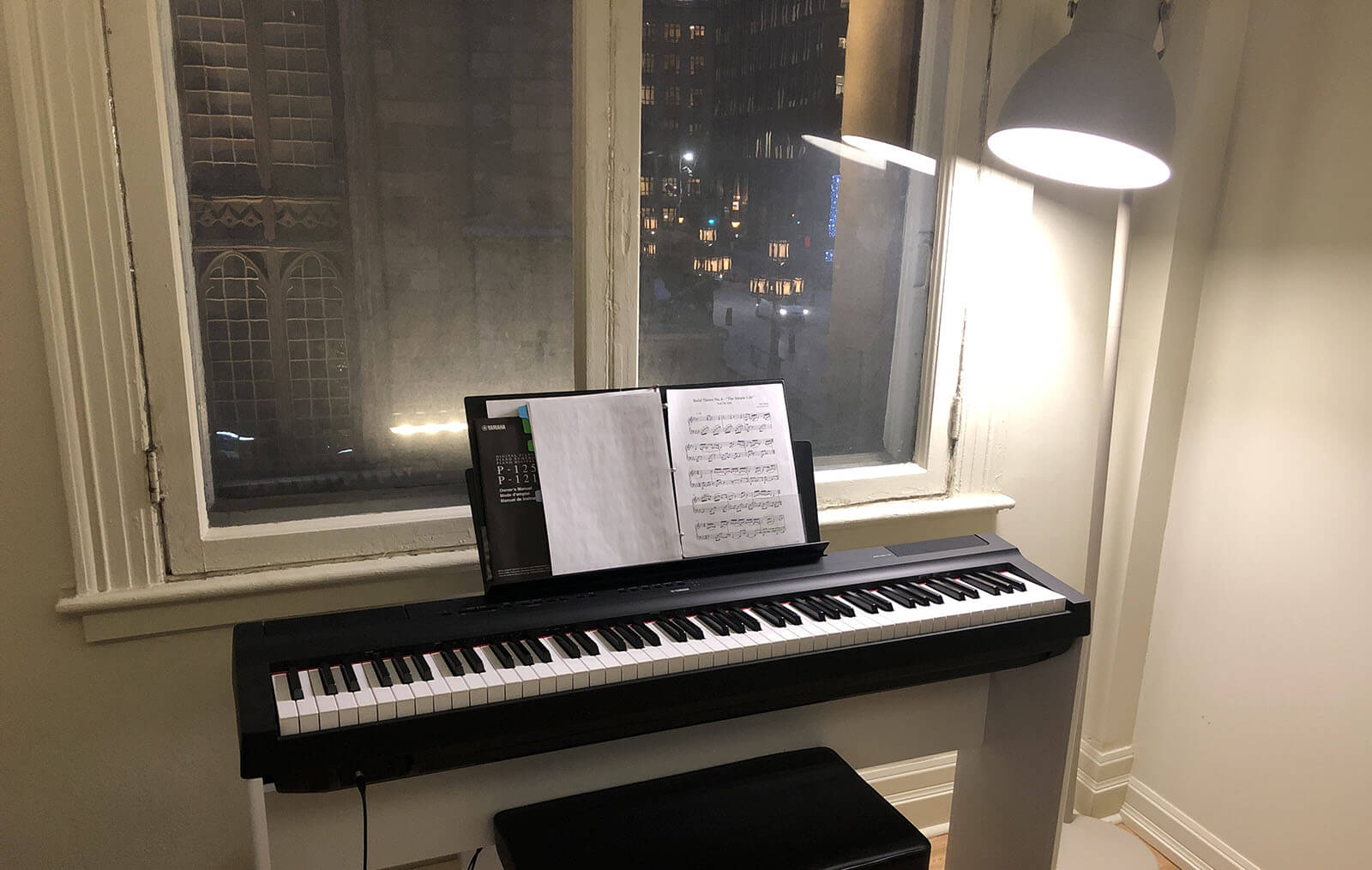 A piano in front of a window