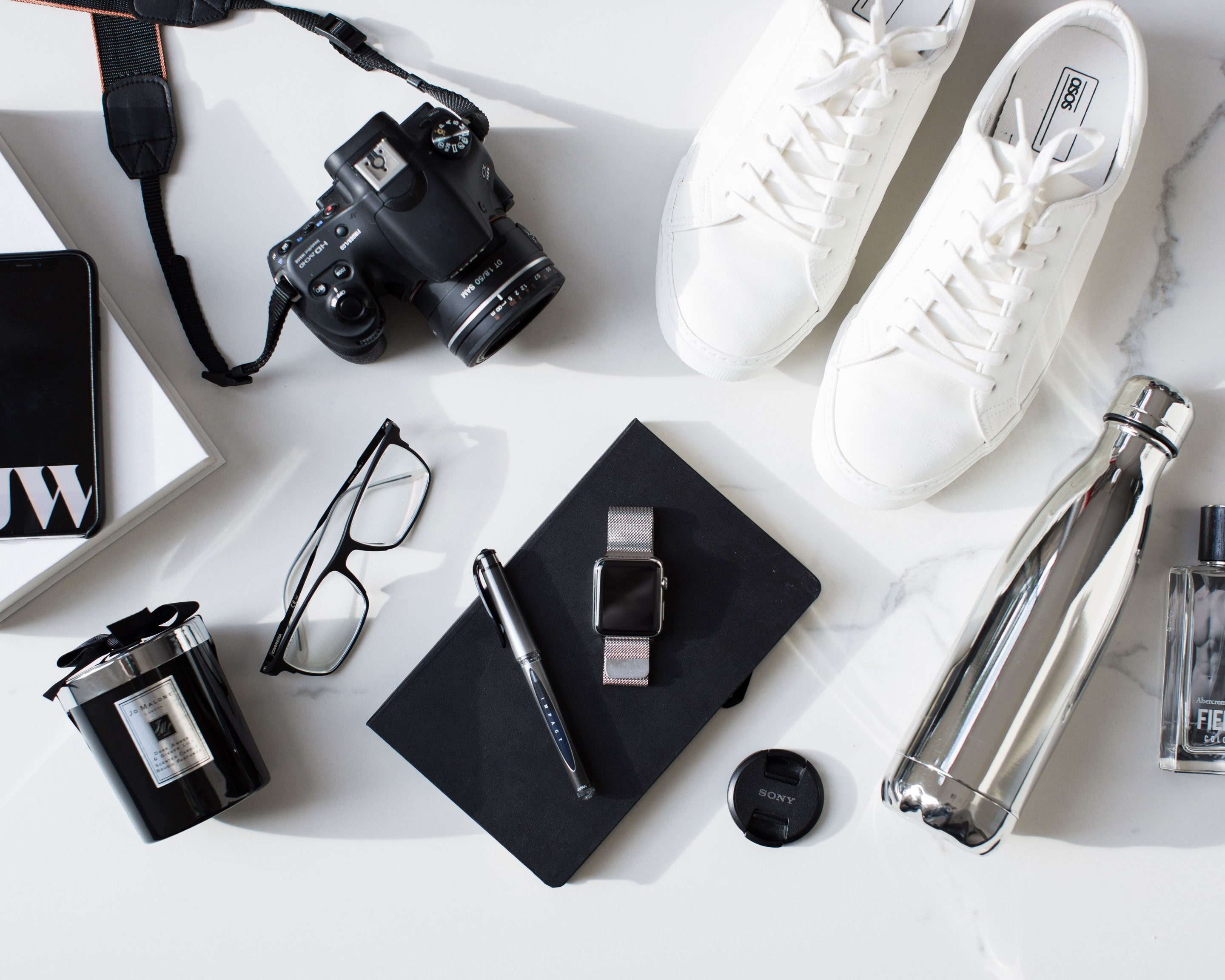 Flat lay of Jack Watkins objects including camera, Apple Watch, Chillys bottle, A&F aftershave, Jo Malone candle, glasses, iPhone and more