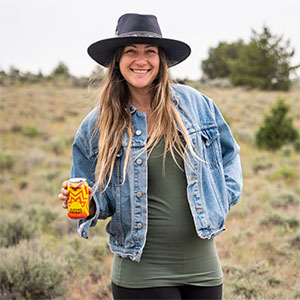 Photo of Amelia Hatcher holding a can of Blazing Bright