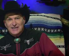 Joe Bob Briggs in Western attire with a bolo tie and Dwight Yoakam hat, arching his eyebrow at the camera.