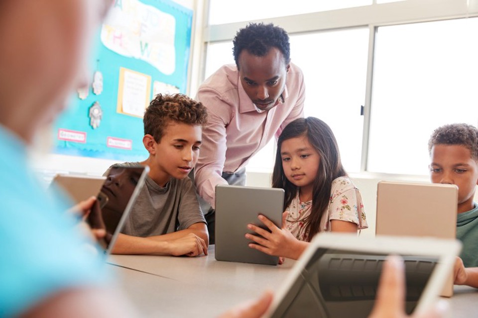 Elementary school instructor working with students with iPads.