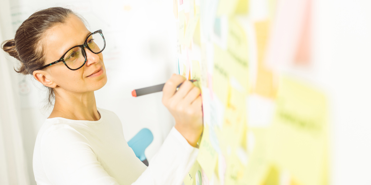 UX designer at a whiteboard, brainstorming for a customer journey map with post-its.
