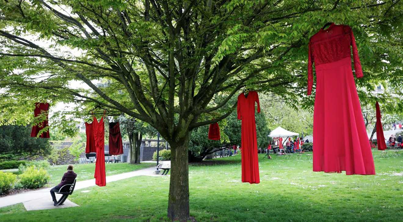 Red dresses are seen hanging on trees to commemorate missing and murdered Indigenous women and girls outside the City Hall in Vancouver, British Columbia, Canada, on May 5, 2021. May 5 is the National Day of Awareness for Missing and Murdered Indigenous Women and Girls in Canada, also known as Red Dress Day.