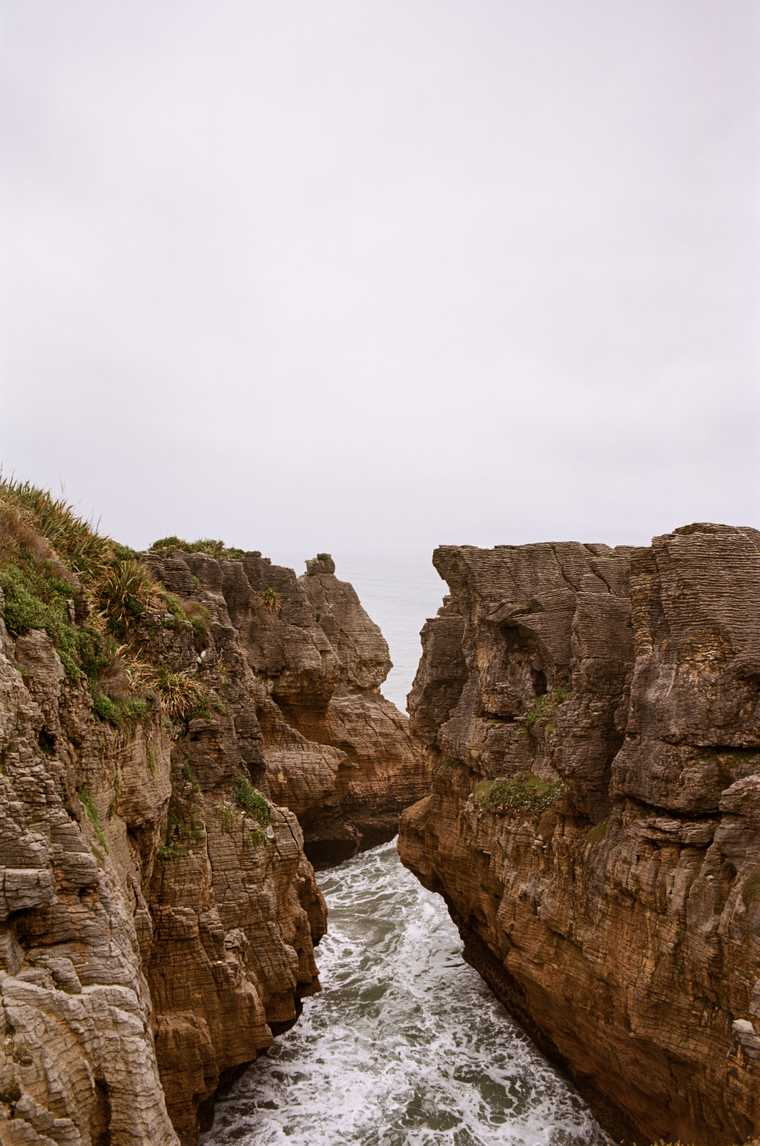Distinctively layered rock formations jut out of the ocean and form a small canyon. The sky is hazy and overcast; the water fades white into the horizon.